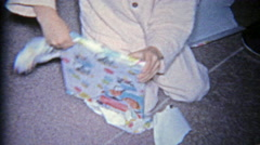 1963: Child opening a religious hymns psalms church book for Christmas gift. - stock footage