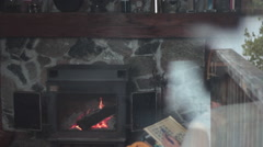 Woman doing crossword beside the fire as seen through window Stock Footage