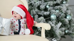 baby sits near a Christmas tree with a gift - stock footage