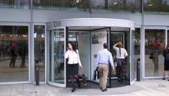 People entering and leaving a venue through a large rotating revolving door Stock Footage