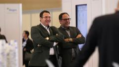 Businessmen talking and laughing at a corporate event or conference Stock Footage