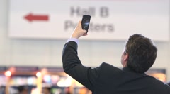 Businessman holding up his camera phone to take a photo Stock Footage
