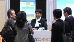 Business people talking at a conference trade show Stock Footage