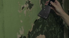 Woman hands removing wallpaper - stock footage