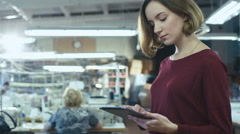 Young woman is standing in a clothing factory and using a tablet - stock footage