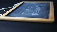 "a stil life of the sentence ""think positive"" written on blackboard - stock footage"
