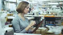 Female is sitting at a table in a clothing factory and sketching on a tablet Stock Footage