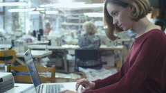 Young female is sitting at a table in a clothing factory and working on a laptop Stock Footage