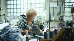 Senior garment worker is working on a sewing machine at a workshop Stock Footage