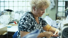 Senior seamstress is working on a sewing machine at a clothing manufactory - stock footage
