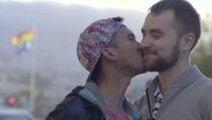 Gay Couple Kiss And Laugh, Gay Pride Flag Blows In Breeze Behind Them Stock Footage