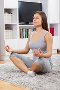 Young woman practicing yoga meditation at home. Fit caucasian female in sport - stock photo