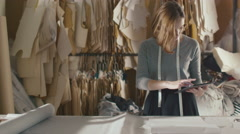 Clothing designer is working with a tablet in a workshop - stock footage
