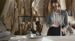 Female clothing designer is photographing sewing patterns with a smartphone Stock Footage