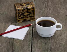 cup of coffee, pencil with paper and a casket, a still life, a subject drinks - stock photo