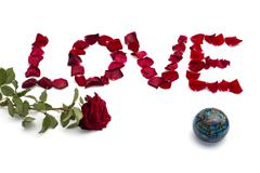 inscription love from petals of roses, and one rose at the left and on the ri - stock photo