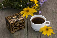 Cup of coffee, wild flowers, casket and yellow flower, still life, on a woode Stock Photos