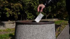 Man throws fake dollars into bin. - stock footage