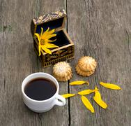 Cup of coffee, open casket with a flower, two linking of cookies and petals Stock Photos