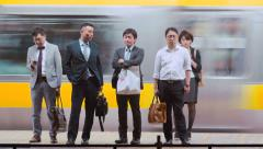 People yawning on the station platform waiting to board trains Stock Footage