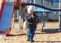 Child shakes off his hands from the sand on playground - stock photo