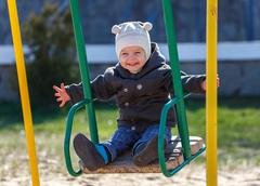 Fearless kid swinging on the swing taking hands free Stock Photos