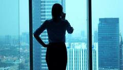 Young businesswoman talking on cellphone standing by window Stock Footage