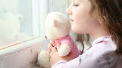 Little girl looking out the window - tracking shot Stock Footage