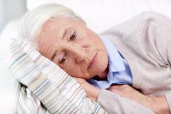 sad senior woman lying on pillow at home - stock photo