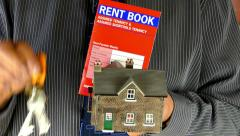 Businessman's hands holding a model house, keys and rent book. Stock Footage