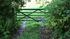 English farm gate green foliage & field Stock Footage