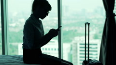 Young businesswoman using smartphone sitting on bed in hotel room Stock Footage