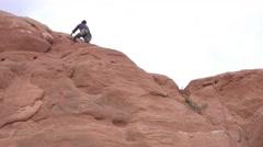 Man climbing redrock in Moab Southern Utah Stock Footage