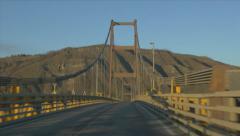 Driving Across Suspension Bridge HandHeld Window Car View Traffic Mountain River - stock footage