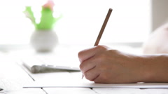 Female artist's hand sketching something with a pencil on a light day Stock Footage