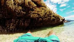 Man enjoying his summer vacation lying on the edge of a seashore Stock Footage