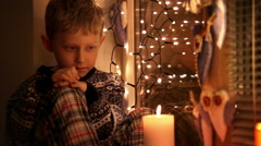 Sad little boy clad in his pajamas and winter-pattern sweater waiting for Santa Stock Footage