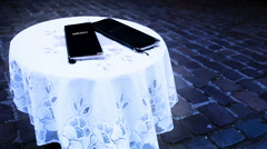 Cold-toned footage of two sets of  the menus lying on the table outdoors Stock Footage