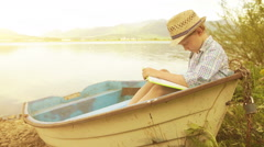 Little fancy clad boy sitting in an old boat reading a book Stock Footage