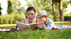 Mother reads a book to her son in the park lying on the rug Stock Footage