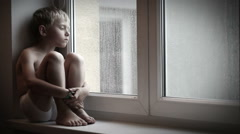 Moody little boy sitting on the windowsill watching raindrops go down the window Stock Footage