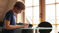 A left-handed male young student working on a creative homework Stock Footage