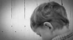 Black and white video: Little worker paints the fence laboriously Stock Footage