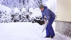Woman shoveling snow near her out-of-town house after an intense snowfall Stock Footage