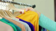 Young woman seller put clothing hangers at the rack, close up HD - stock footage