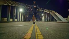 Man running in the middle historic 6th Street Bridge viaduct Los Angeles night Stock Footage