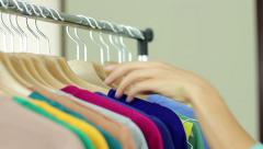 Young woman take hangers with clothes from the rack, close up HD Stock Footage