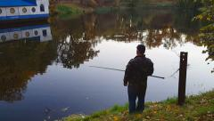 An elderly man is fishing at the lake Stock Footage