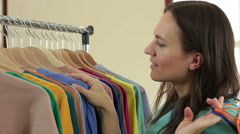 Female customer choosing clothes from rack in clothing store HD Stock Footage