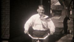 2666 - dad rides a bike on suburban sidewalks & street - vintage film home movie Stock Footage